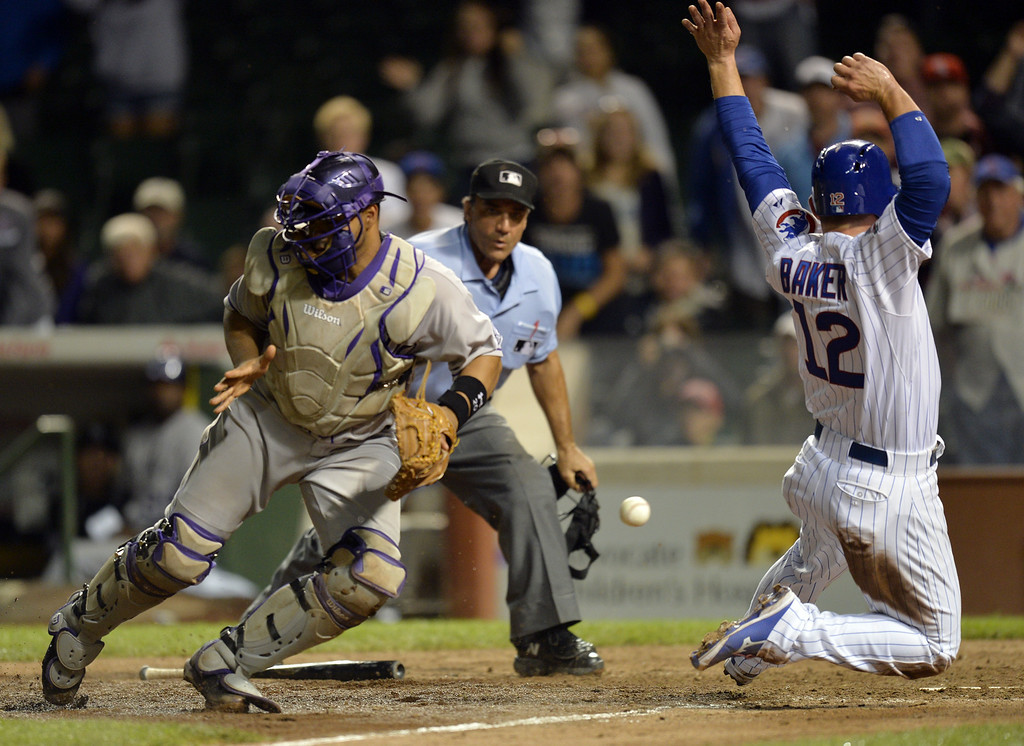 . John Baker #12 of the Chicago Cubs (R) scores past catcher Wilin Rosario #20 of the Colorado Rockies on a game-winning sacrifice fly hit by Starlin Castro during the 16th inning on July 30, 2014 at Wrigley Field in Chicago, Illinois. The Cubs defeated the Rockies 4-3 in 16 innings.  (Photo by Brian Kersey/Getty Images)