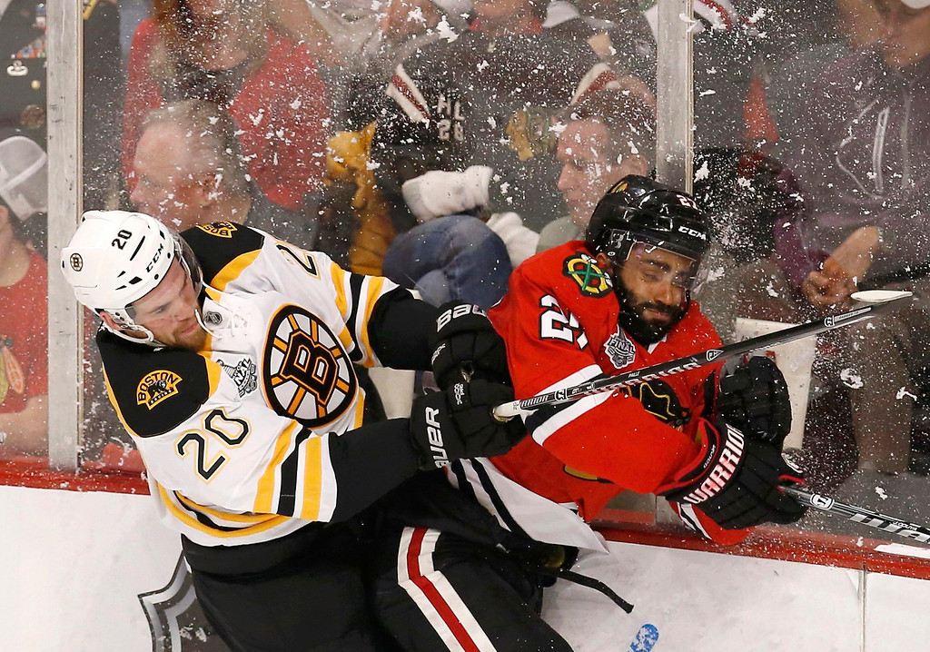 . Boston Bruins\' Daniel Paille (L) checks Chicago Blackhawks\' Johnny Oduya during the first period in Game 1 of their NHL Stanley Cup Finals hockey game in Chicago, Illinois, June 12, 2013. REUTERS/Jim Young