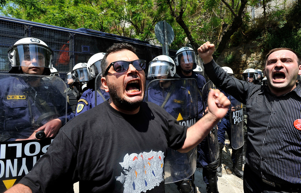 . Two men shout as police clash with protesters at the annual rally to protest the mass killings of Armenians in Ottoman Turkey nearly a century ago in Thessaloniki, Greece on Wednesday April 24, 2013. About 250 protesters, mostly from Greek-Armenian groups, gathered outside the Turkish consulate. About 20 countries worldwide, including Greece, as well as the European parliament recognize the mass killings as an act of genocide, despite strong objections from Turkey. (AP Photo/Nikolas Giakoumidis)
