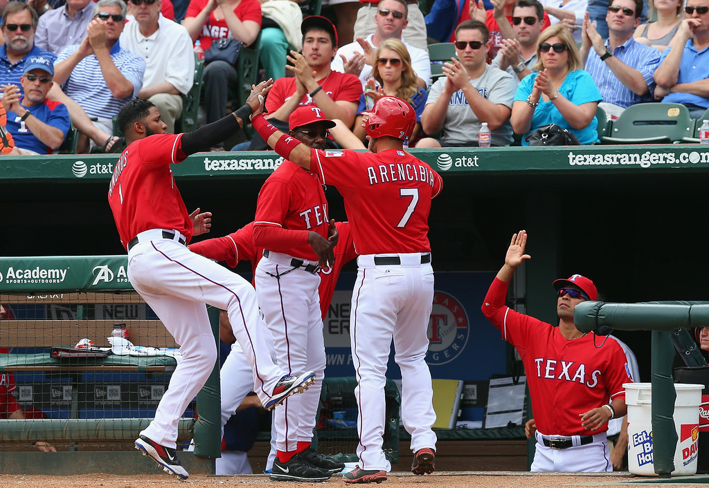 . Arencibia #7 of the Texas Rangers celebrates a run with Elvis Andrus #1 against the Philadelphia Phillies in the 5th inning during the MLB Opening Day game at Globe Life Park in Arlington on March 31, 2014 in Arlington, Texas.  (Photo by Ronald Martinez/Getty Images)