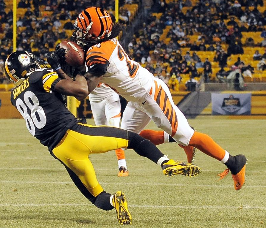 . Cincinnati Bengals cornerback Adam Jones, top, intercepts a pass to Pittsburgh Steelers wide receiver Emmanuel Sanders (88) in the third quarter of an NFL football game on Sunday, Dec. 15, 2013, in Pittsburgh. (AP Photo/Don Wright)