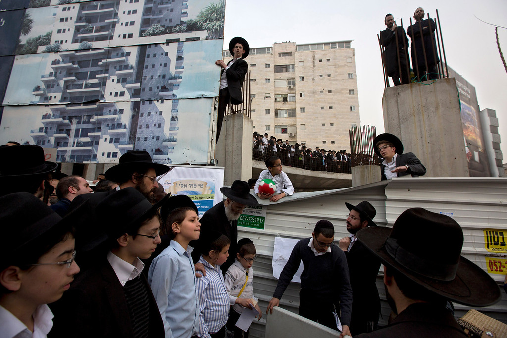 . Ultra-Orthodox Jewish men participate in a rally against plans to force them to serve in the Israeli military, blocking roads and paralyzing the city of Jerusalem, Sunday, March 2, 2014. The widespread opposition to the compulsory draft poses a challenge to the country, which is grappling with a cultural war over the place of the ultra-Orthodox in Israeli society. With secular Jews required to serve, the issue is one of the most sensitive flashpoints between Israel\'s secular majority and its devout minority. (AP Photo/Sebastian Scheiner)