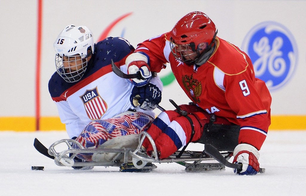 . Nikko Landeros of the United States is challenged by Konstantin Shikhov of Russia during the Ice Sledge Hockey Gold Medal game between the United States and Russia on day eight of the Sochi 2014 Paralympic Winter Games at Shayba Arena on March 15, 2014 in Sochi, Russia.  (Photo by Dennis Grombkowski/Getty Images)