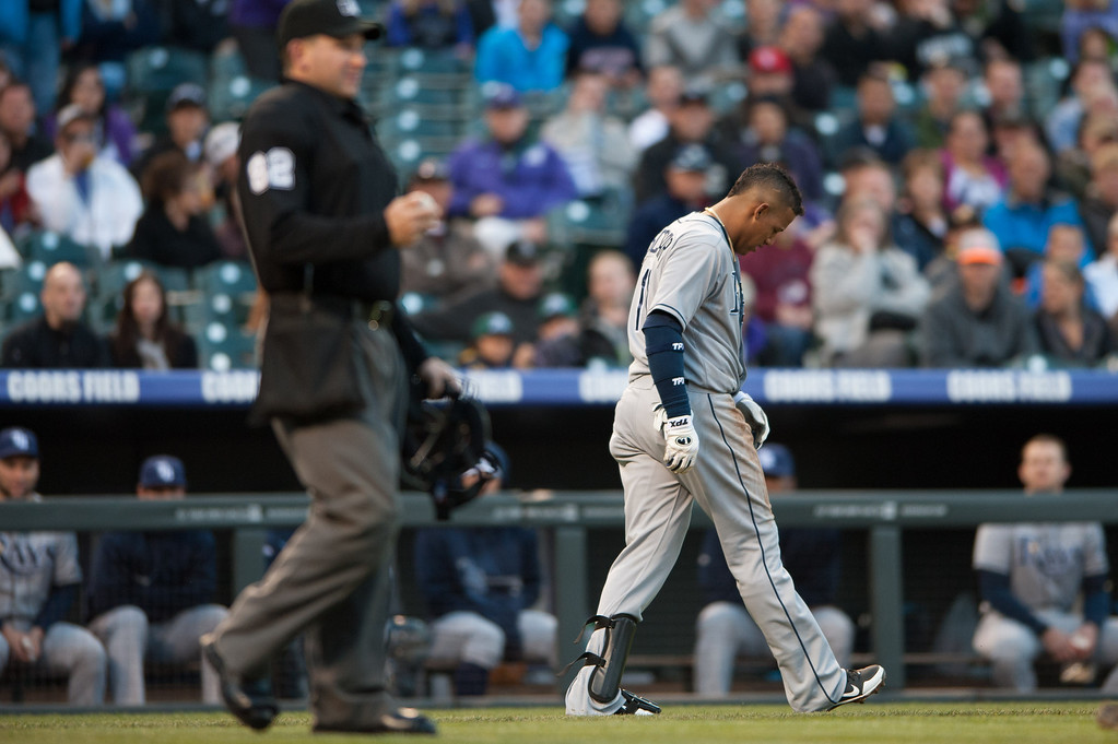 . DENVER, CO - MAY 4:  Yunel Escobar #11 of the Tampa Bay Rays reacts after being hit by a pitch by Jon Garland #27 of the Colorado Rockies in the second inning of a game at Coors Field on May 4, 2013 in Denver, Colorado. The Rockies led the Rays 1-0 after one inning. (Photo by Dustin Bradford/Getty Images)