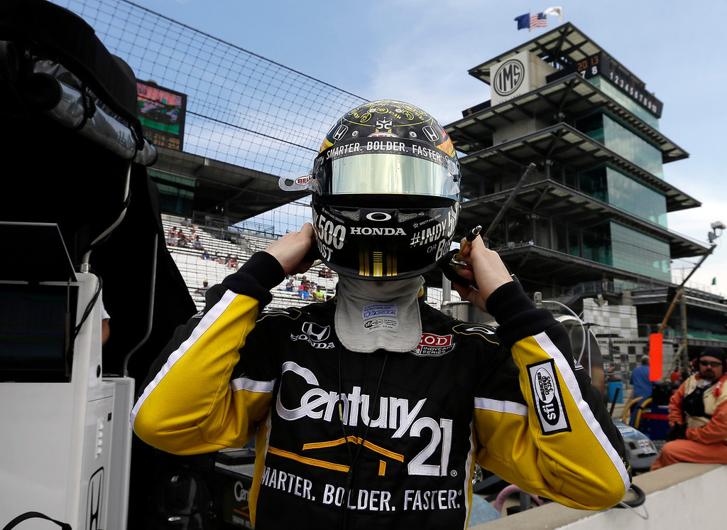 . Josef Newgarden dons his helmet as he prepares to drive during practice for the Indianapolis 500 auto race at the Indianapolis Motor Speedway in Indianapolis, Thursday, May 16, 2013. (AP Photo/Darron Cummings)