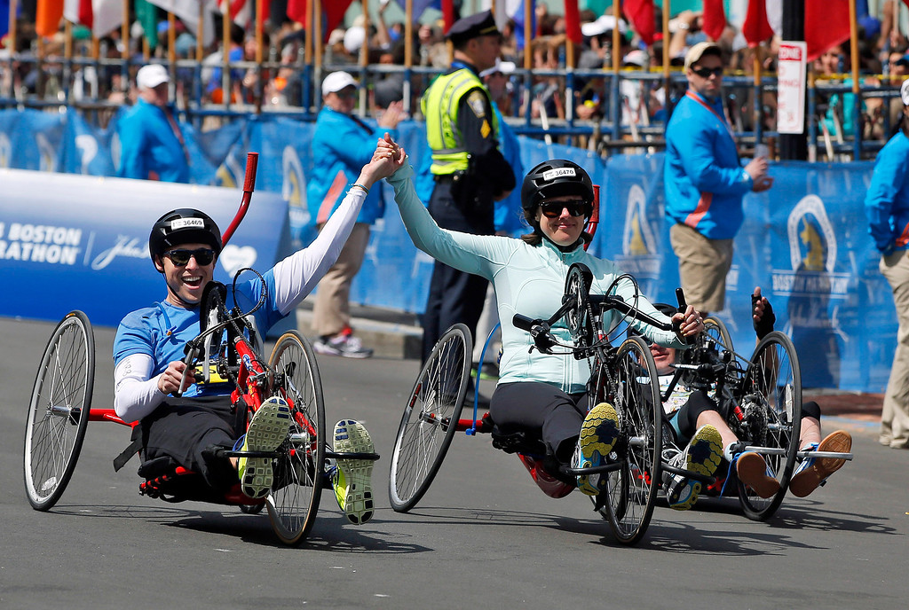 . Boston Marathon husband and wife bombing survivors Patrick Downes and Jessica Kensky, who each lost a leg in last year\'s bombings, roll across the finish line in the 118th Boston Marathon Monday, April 21, 2014 in Boston. (AP Photo/Elise Amendola)