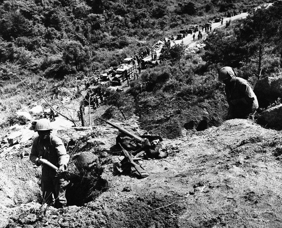 . American soldiers (foreground) dig in to set up a machine gun position on side of ridge overlooking a vital supply road in the central sector near Kumsong, Korea on July 20, 1953. In the background, trucks and vehicles with men and supplies prepare to move Northward in the area from which they had withdrawn during heavy Chinese attacks. (AP Photo/George Sweers)