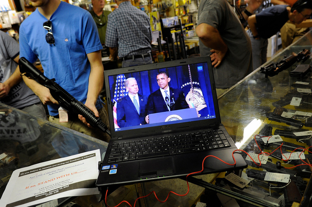 . Gun shop customers shop for weapons as they listen to live streaming video of an announcement about gun control by U.S. President Barack Obama at the Bullet Hole gun shop in Sarasota, Florida January 16, 2013. REUTERS/Brian Blanco