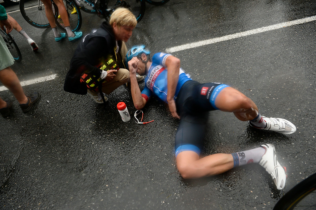 . A doctor tends to New Zealand\'s Jack Bauer  after he crashed in the last three kilometers of the nineteenth stage of the Tour de France cycling race over 208.5 kilometers (129.6 miles) with start in Maubourguet and finish in Bergerac, France, Friday, July 25, 2014. (AP Photo/Lionel Bonaventure, Pool)