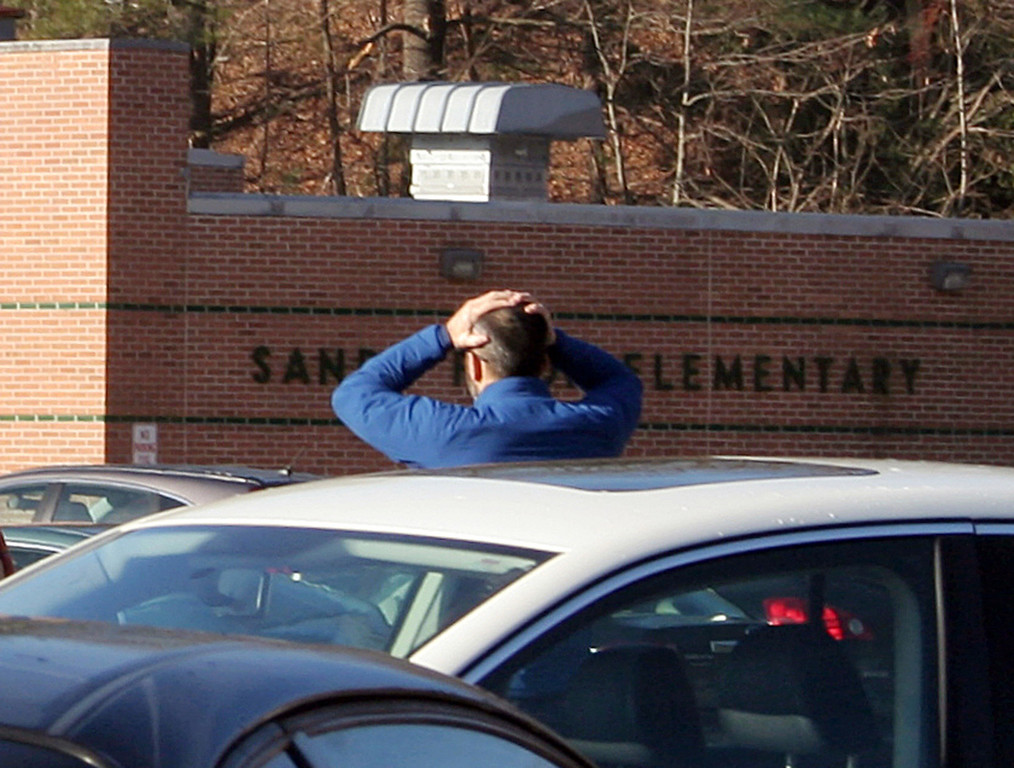 . In this photo provided by the Newtown Bee, a man stands with his hands on his head outside of Sandy Hook Elementary School in Newtown, Conn., where authorities say a gunman opened fire, killing 26 people, including 20 children, Friday, Dec. 14, 2012. (AP Photo/Newtown Bee, Shannon Hicks)