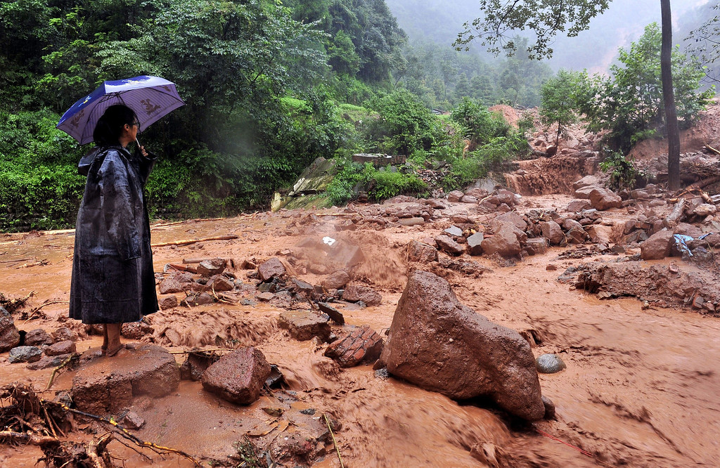 . A woman looks on after a landslide triggered by heavy rainstorm hit Shanxi village of Zhongxing township in Dujiangyan, southwest China\'s Sichuan province on July 10, 2013. Between 30 and 40 people were buried by a landslide in southwest China on Wednesday, local officials said, as heavy rains in the area also destroyed homes and bridges.  STR/AFP/Getty Images