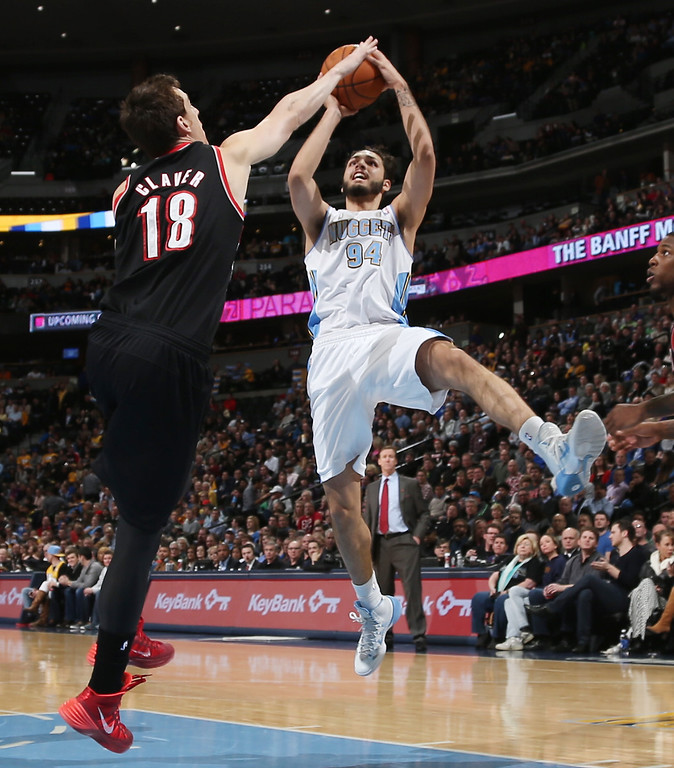 . Portland Trail Blazers forward Victor Claver, left, of Spain, goes up to block a shot by Denver Nuggets guard Evan Fournier, of France, in the third quarter of an NBA basketball game in Denver, Tuesday, Feb. 25, 2014. Portland won 100-95. (AP Photo/David Zalubowski)