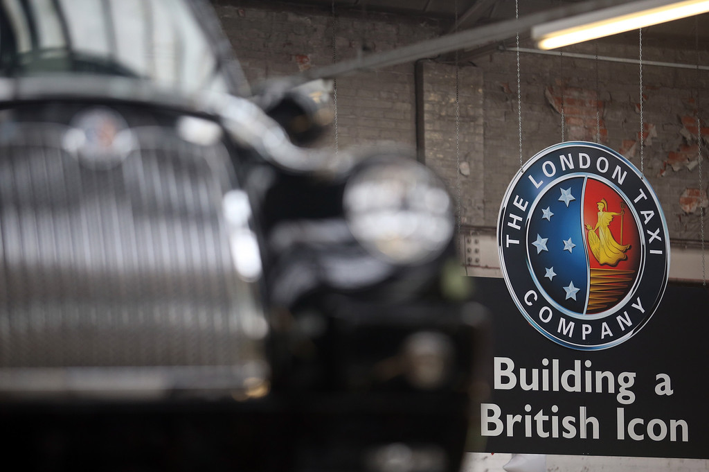 . Signage hangs inside the factory of The London Taxi Company beside a completed TX4 (Euro 5) London Taxi cab on September 11, 2013 in Coventry, England.  (Photo by Matt Cardy/Getty Images)