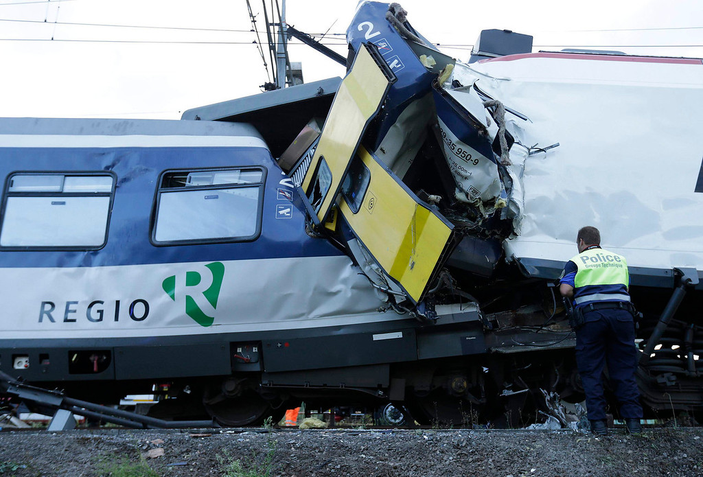 . A police officer looks at the damage after a head on collision between two trains near Granges-pres-Marnand, near Payerne in western Switzerland, July 29, 2013. The two trains collided at Granges-pr�s-Marnand in the Swiss canton of Vaud on Monday evening, injuring about 40 people, four seriously, Swiss news agency ATS reported. There was no immediate report of any deaths in the crash. REUTERS/Denis Balibouse  (SWITZERLAND - Tags: DISASTER TRANSPORT)