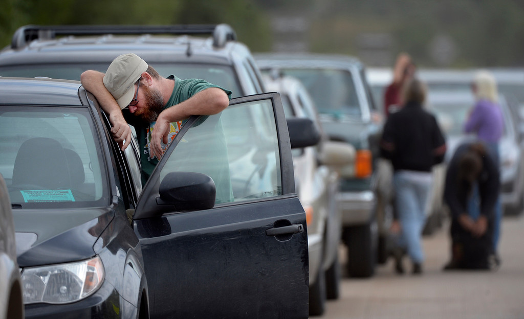 ". LYONS, CO. - SEPTEMBER 19: Lyons resident Perry Corn waits with his wife, Angie, at a checkpoint at the junction of highways 66 & 36 in Lyons, CO September 18, 2013. He said, ""we\'re going to see what we can salvage and make sure no one runs off with the rest. We tried to tough it out till Saturday but with 3 dogs and the 2 of us we decided to heed the warnings.\"" Now staying with friends he concluded, \""my belief in the human spirit has been rejuvenated we\'e been so fortunate to have great people around us, taking care of us.\"" Residents were being allowed to return to their homes Thursday. (Photo By Craig F. Walker / The Denver Post)"