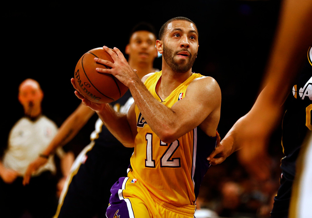 . epa04007703 Los Angeles Lakers Kendall Marshall (C) drives to the basket against the Utah Jazz in the first half action of their NBA game at Staples Center in Los Angeles, California USA, 03 January 2014.  EPA/PAUL BUCK CORBIS OUT