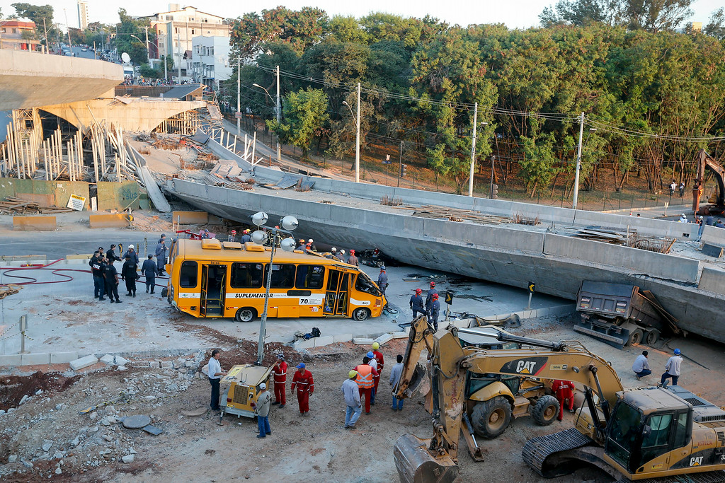 . A bus sits damaged next to a bridge after it collapsed in Belo Horizonte, Brazil, Thursday, July 3, 2014. The overpass under construction collapsed Thursday in the Brazilian World Cup host city. The incident took place on a main avenue, the expansion of which was part of the World Cup infrastructure plan but, like most urban mobility projects related to the Cup, was not finished on time for the event. (AP Photo/Victor R. Caivano)