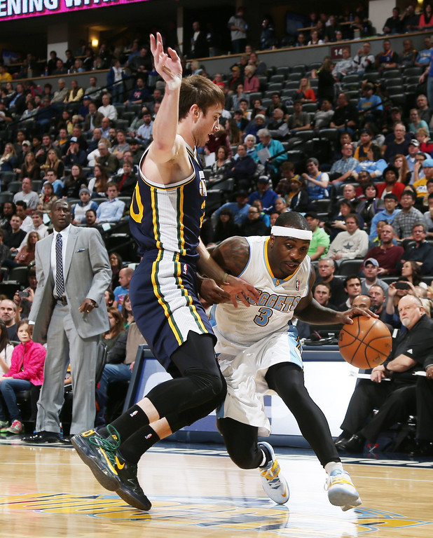 . Denver Nuggets guard Ty Lawson, right, works the ball inside for shot as Utah Jazz guard Gordon Hayward covers in the first quarter of an NBA basketball game in Denver on Friday, Dec. 13, 2013. (AP Photo/David Zalubowski)