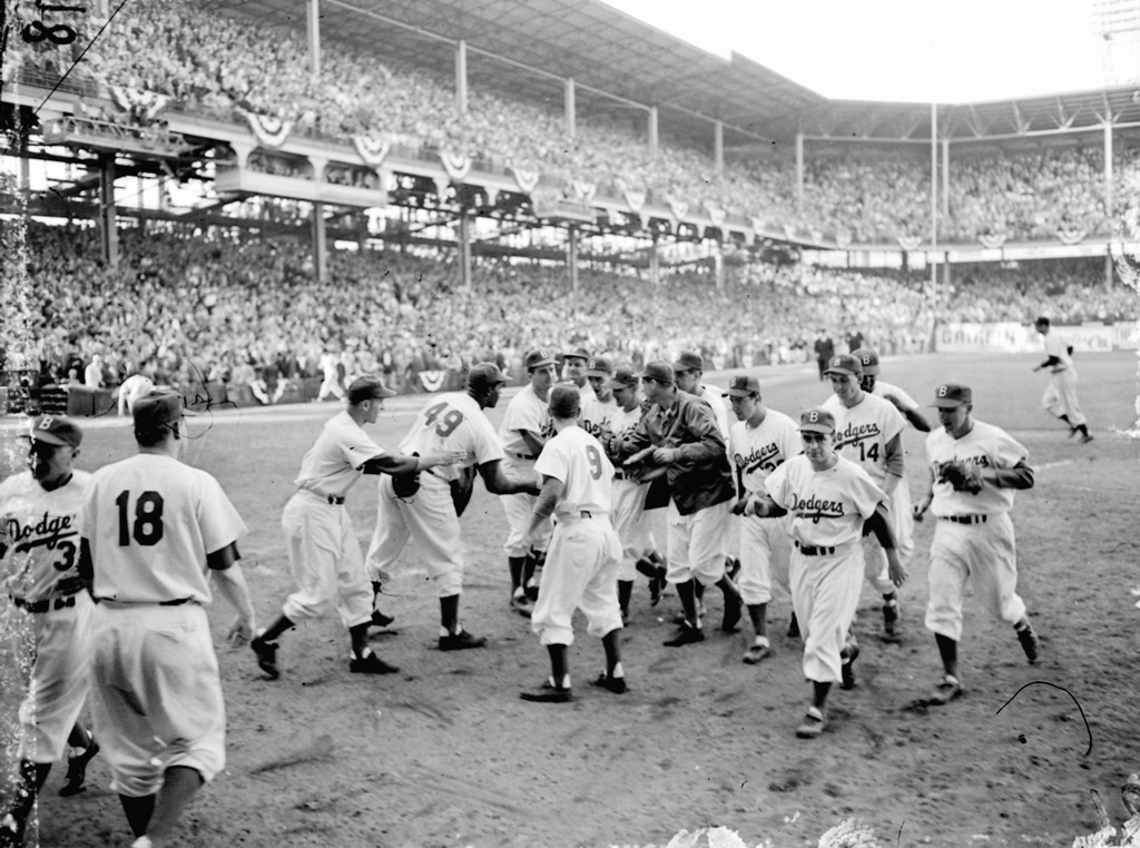 . Dodger players rush to congratulate Carl Erskine, fourth from right, after he completed a very brilliant pitching job against the Yankees in the third game of the World Series at Ebbets Field in Brooklyn, N.Y., on October 2, 1953.  Erskine held the Yankees to six hits, struck out 14 for an all-time series record, and won the game 3-2.  Dodgers are, from left to right:  George Shuba, Joe Black (49), Erv Palica, Don Zimmer (9), coach Cookie Lavagetto, background, Dick Williams, Erskine, Preacher Roe, Wayne Belardi, Bill Antonello, bat boy, Gil Hodges, Jackie Robinson, rear, and Pee Wee Reese. (AP Photo)