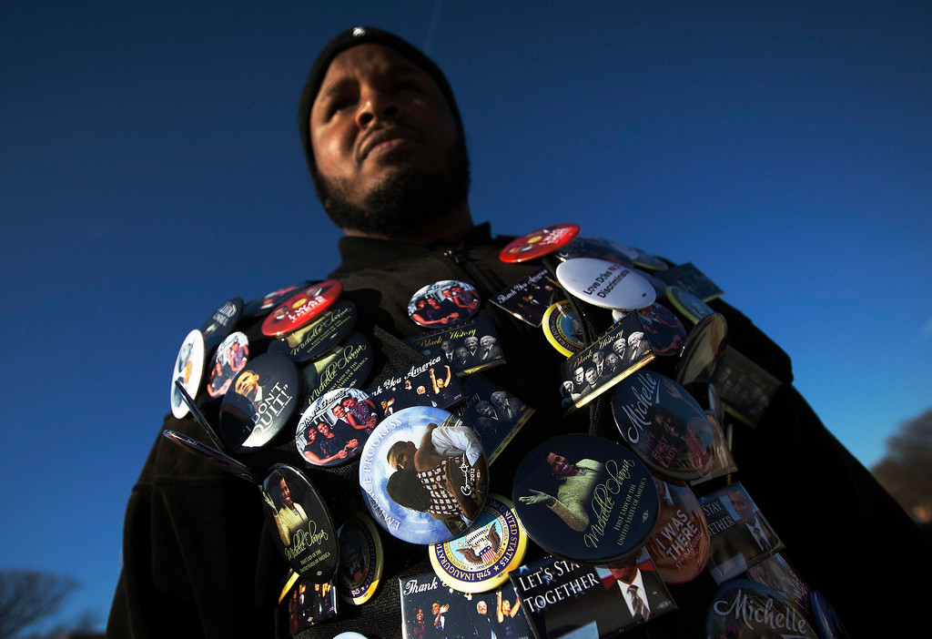. Tajidddin Ahmed of Atlanta, who is attending tomorrow\'s inauguration, wears a jacket filled with buttons in support of U.S. President Barack Obama as he stands on the National Mall in Washington January 20, 2013. U.S. Vice President Joe Biden took the oath of office for his second term on Sunday at a small ceremony at his official residence, using a bible with a Celtic cross on the cover that has been in his family since 1893. The U.S. Constitution requires the president and vice president to be sworn in on January 20. Obama is slated to take his oath at a small ceremony at the White House at 11:55 a.m. REUTERS/Shannon Stapleton