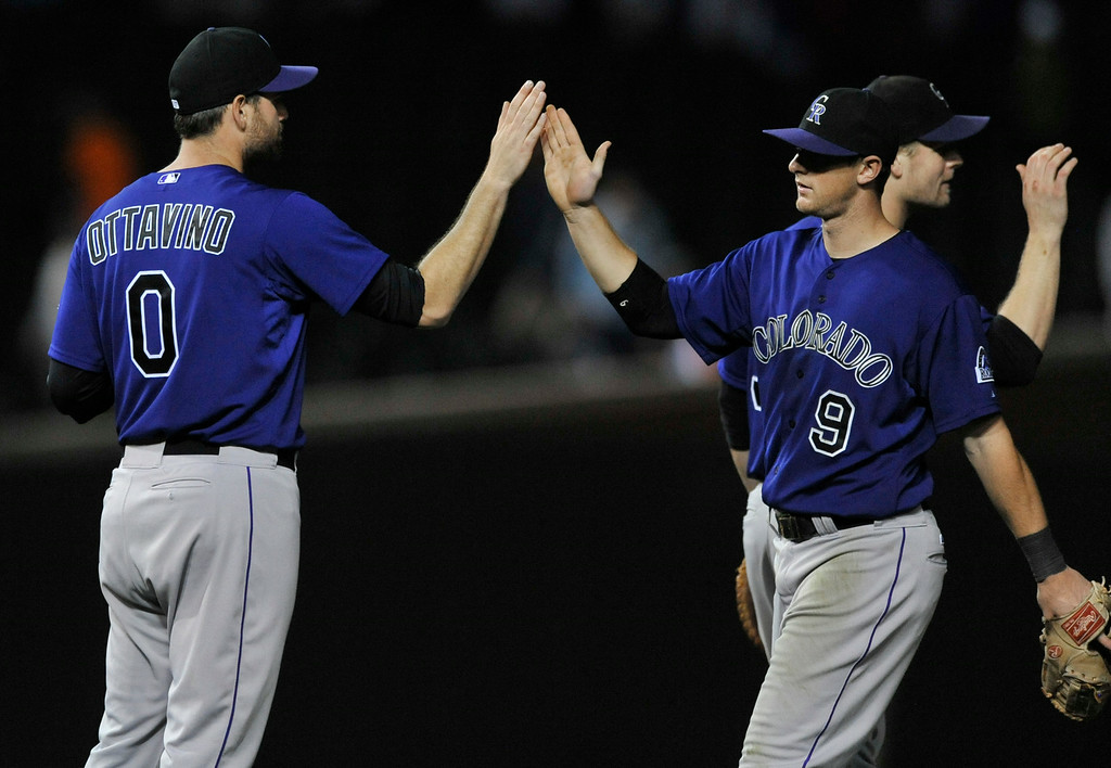 . Colorado Rockies closing pitcher Adam Ottavino (0), celebrates with teammate D.J. LeMahieu (9), after defeating the Chicago Cubs 6-4 in ten innings of a baseball game in Chicago, Wednesday, July 30, 2014. (AP Photo/Paul Beaty)