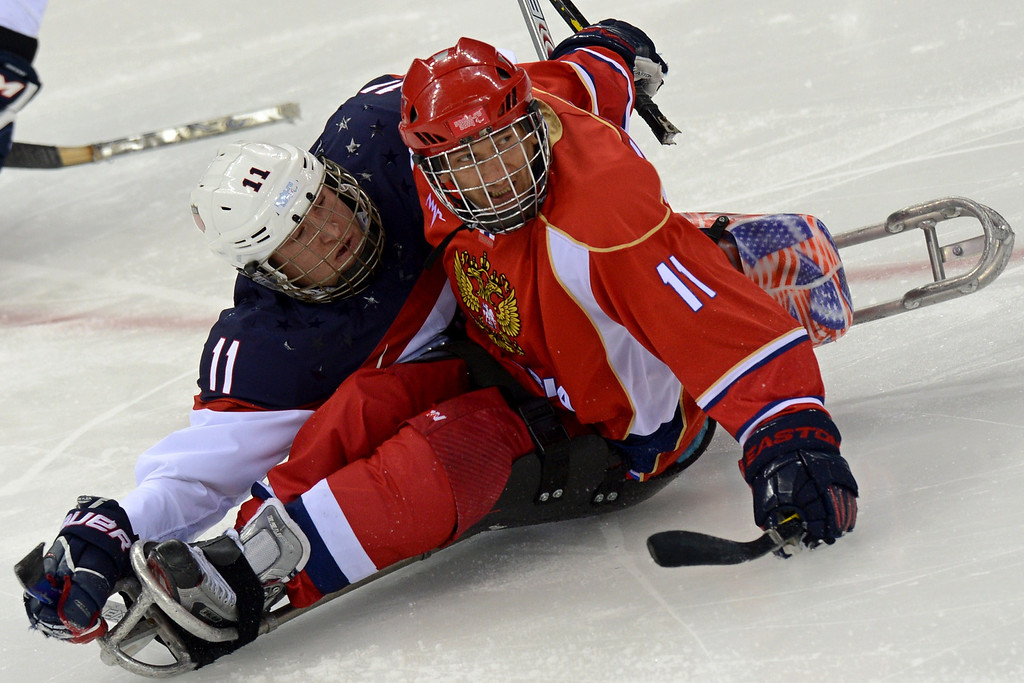 . United States\' Tyler Carron (L) vies Russia\'s Alexey Amosov  during Sledge Hockey Final match between Russia and USA at XI Paralympic Olympic games in the Shayba stadium close near Sochi on March 15, 2014. AFP PHOTO/KIRILL  KUDRYAVTSEV/AFP/Getty Images