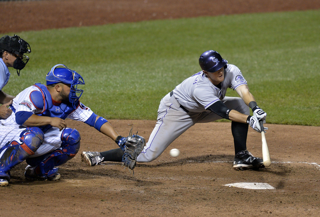. DJ LeMahieu #9 of the Colorado Rockies fails to connect on a suicide squeeze bunt during the tenth inning against the Chicago Cubs on July 29, 2014 at Wrigley Field in Chicago, Illinois.  (Photo by Brian Kersey/Getty Images)