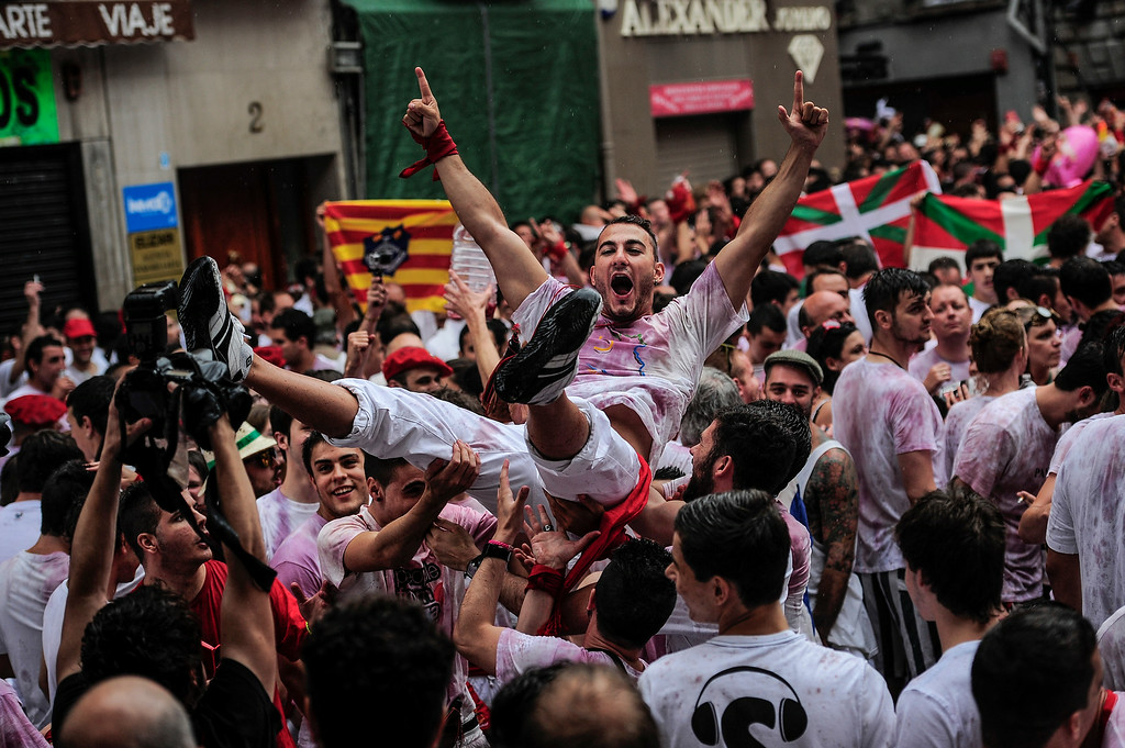 ". Revelers celebrate during the launch of the \'Chupinazo\' rocket, to celebrate the official opening of the 2014 San Fermin fiestas, in Pamplona, Spain, Sunday, July 6, 2014. Revelers from around the world kick off the festival with a messy party in the Pamplona town square, one day before the first of eight days of the running of the bulls glorified by Ernest Hemingway\'s 1926 novel ""The Sun Also Rises.\"" (AP Photo/Alvaro Barrientos)"
