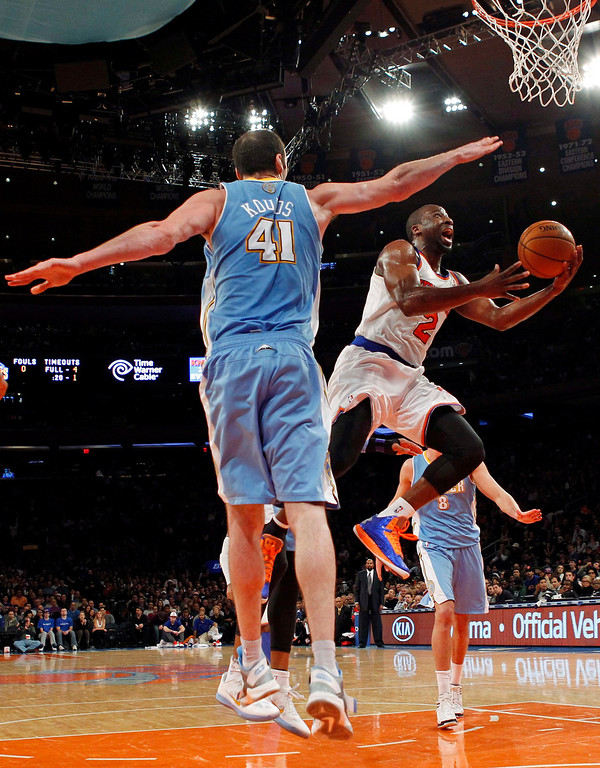 . New York Knicks point guard Raymond Felton drives to the basket past Denver Nuggets center Kosta Koufos in the third quarter of their NBA basketball game at Madison Square Garden in New York, December 9, 2012.    REUTERS/Adam Hunger  (UNITED STATES - Tags: SPORT BASKETBALL)