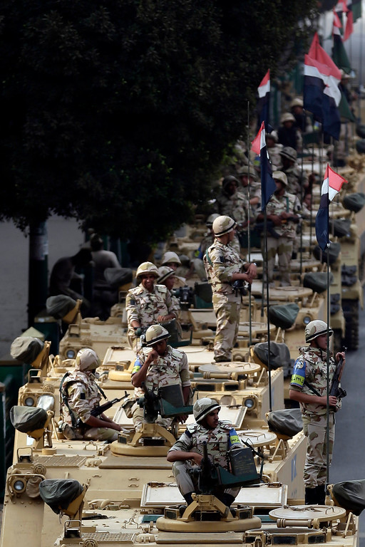 . Aug. 16, 2013: Egyptian army soldiers take their positions on top and next to their armored vehicles while guarding an entrance to Tahrir Square, in Cairo, Friday, Aug. 16, 2013. Heavy gunfire rang out throughout Cairo as tens of thousands of Muslim Brotherhood supporters clashed with armed vigilantes in the fiercest street battles to engulf the capital since the country\'s Arab Spring uprising. The clashes killed 173 people nationwide, including police officers. (AP Photo/Hassan Ammar)