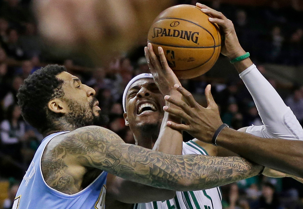 . Boston Celtics forward Paul Pierce, right, goes to the hoop against Denver Nuggets guard Wilson Chandler, left, during the first half of an NBA basketball game in Boston, Sunday, Feb. 10, 2013. (AP Photo/Elise Amendola)