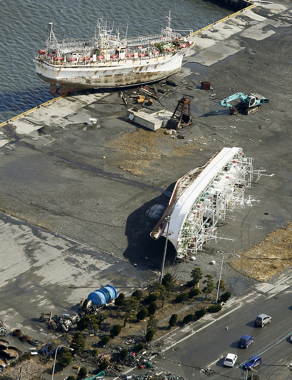 . Fishing boats drifted by tsunami sit on a pier near a port in Hachinohe, Aomori Prefecture, Saturday morning, March 12, 2011 after Japan\'s biggest recorded earthquake slammed into its eastern coast Friday. (AP Photo/Kyodo News)
