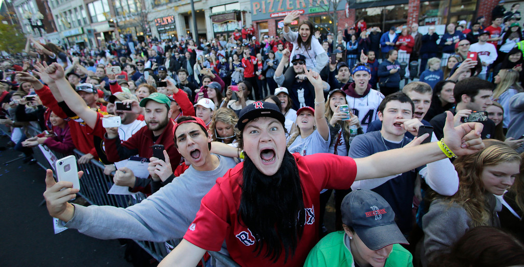 . Boston Red Sox fans celebrate during a parade in celebration of the baseball team\'s World Series victoru, Saturday, Nov. 2, 2013, in Boston. (AP Photo/Charles Krupa)