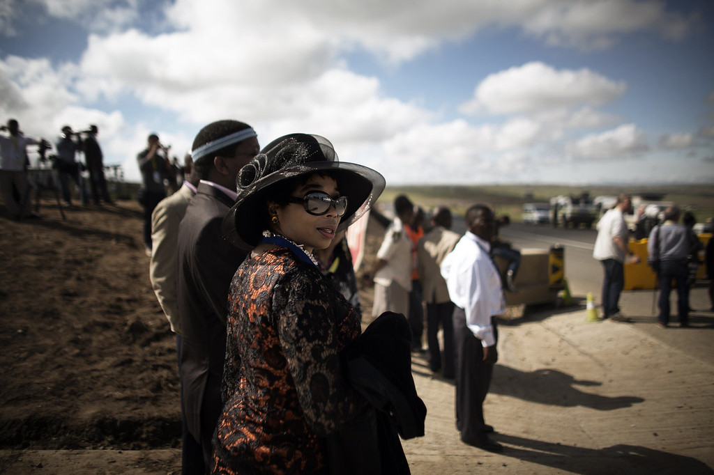 . Guests wait to be bused to the location of the funeral ceremony of South African former president Nelson Mandela in Qunu on December 15, 2013. South Africa\'s first black president Nelson Mandela received a tearful state funeral at his childhood village of Qunu on Sunday, followed by a traditional burial attended by family and friends. Mandela, the revered icon of the anti-apartheid struggle in South Africa and one of the towering political figures of the 20th century, died in Johannesburg on December 5 at age 95.  AFP PHOTO / MARCO LONGARIMARCO LONGARI/AFP/Getty Images