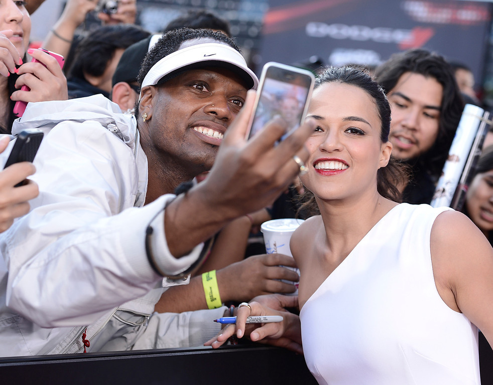 """. Actress Michelle Rodriguez poses for a photo with a fan at the LA Premiere of the \""""Fast & Furious 6\"""" at the Gibson Amphitheatre on Tuesday, May 21, 2013 in Universal City, Calif. (Photo by Dan Steinberg/Invision/AP)"""