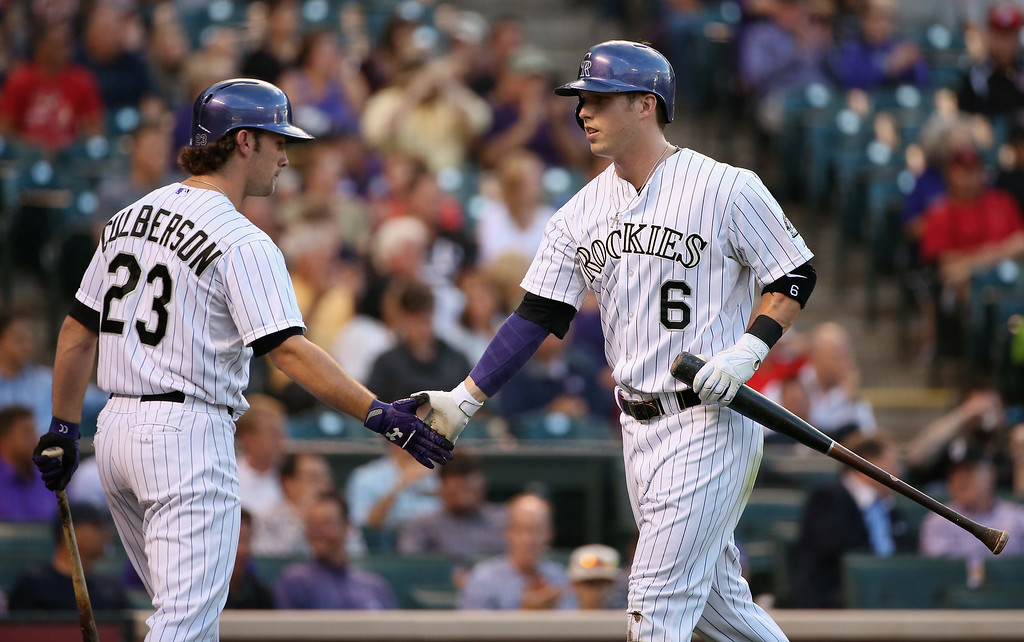 . DENVER, CO - AUGUST 14:  Corey Dickerson #6 of the Colorado Rockies celebrates with Charlie Culberson #23 of the Colorado Rockies after scoring on a double by Wilin Rosario #20 of the Colorado Rockies as the Cincinnati Reds held a 2-1 lead in the second inning at Coors Field on August 14, 2014 in Denver, Colorado.  (Photo by Doug Pensinger/Getty Images)