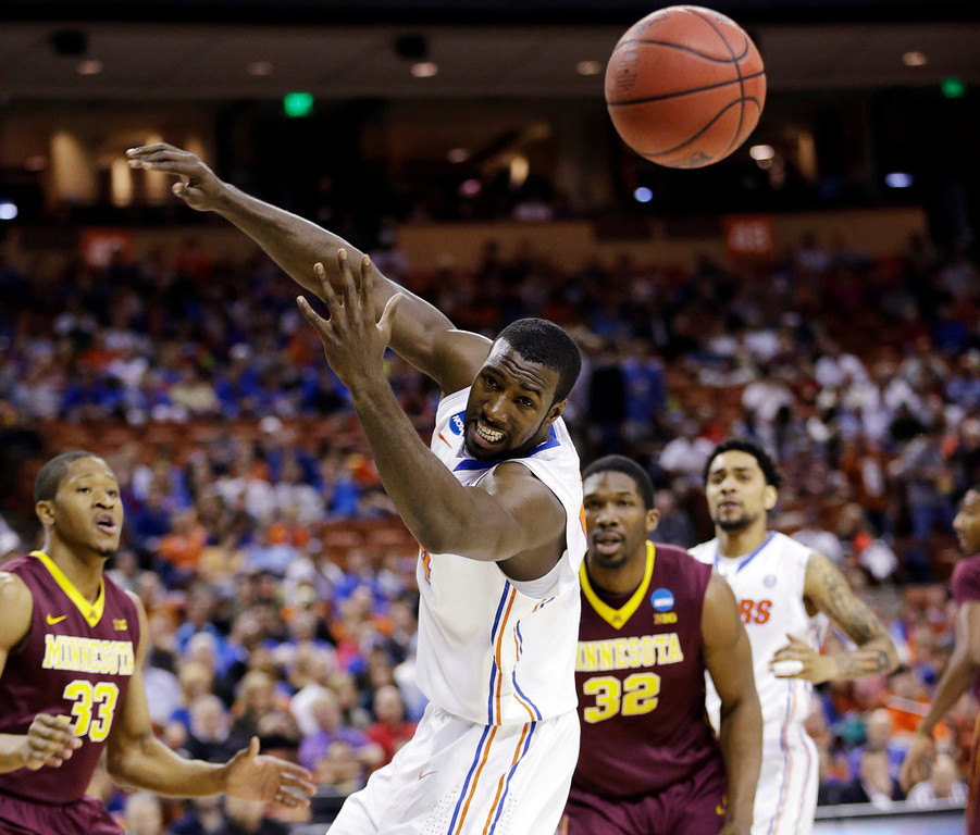 . Florida\'s Patric Young, center, loses cotrol of a pass as Minnesota\'s Rodney Williams (33) and Trevor Mbakwe (32) watch during the first half of a third-round game of the NCAA college basketball tournament, Sunday, March 24, 2013, in Austin, Texas. (AP Photo/Eric Gay)