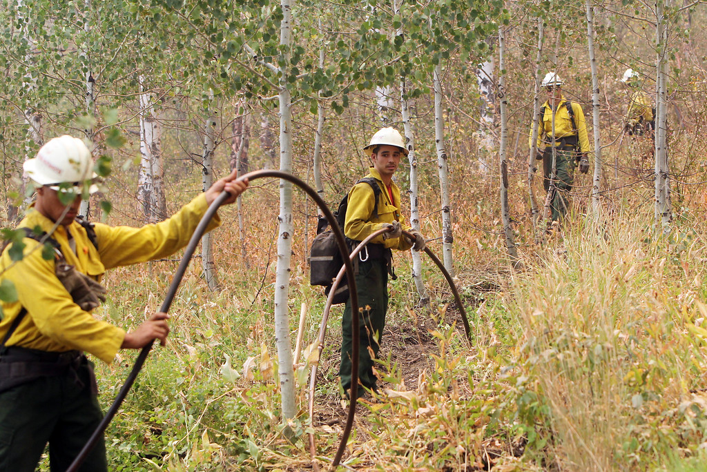 . Members of the Ironwood Hot Shots from Tuscon, Ariz. work a water line behind homes as the Elk Complex fire burns in Pine, Idaho on Monday, Aug. 12, 2013. (AP Photo/The Idaho Statesman, Joe Jaszewski)