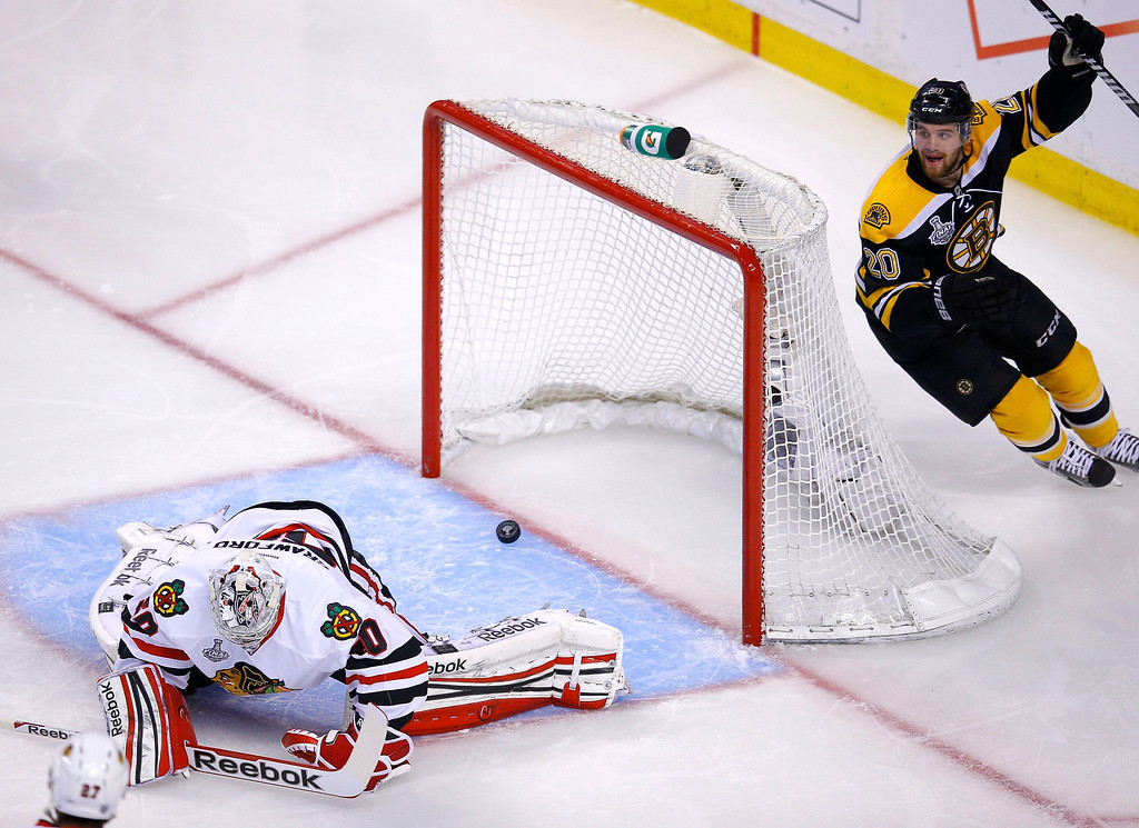 . Boston Bruins\' Daniel Paille (R) celebrates a goal by teammate Patrice Bergeron (not pictured) on Chicago Blackhawks goalie Corey Crawford during the third period in Game 4 of their NHL Stanley Cup Finals hockey series in Boston, Massachusetts, June 19, 2013. REUTERS/Brian Snyder