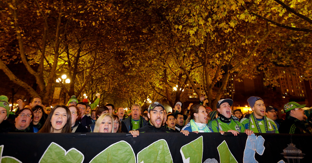 ". Members of the Emerald City Supporters cheer for the Seattle Sounders as they take part in the ""March to the Match\"" before a knockout-round match against the Colorado Rapids in the MLS Cup soccer playoffs Wednesday, Oct. 30, 2013, in Seattle. (AP Photo/Ted S. Warren)"