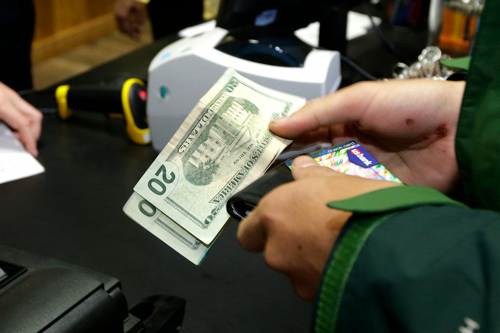 . A customer pays for his recreational marijuana purchase at Top Shelf Cannabis, Tuesday, July 8, 2014, in Bellingham, Wash., on the first day of legal sales in the state.  (AP Photo/Ted S. Warren)