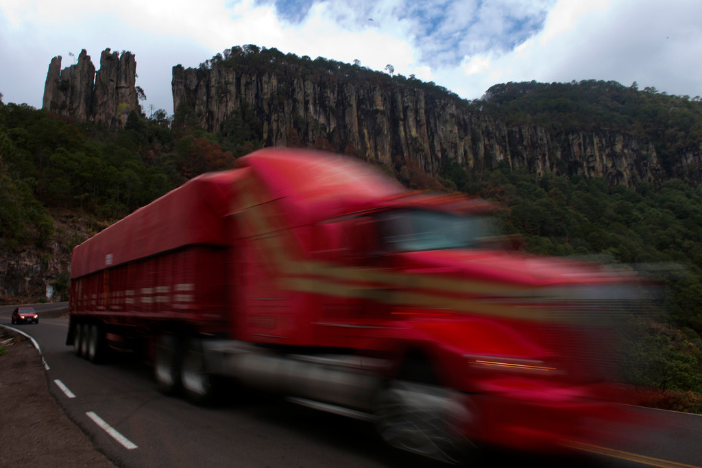 . In this June 12, 2013 photo, a cargo truck whizzes past on the new Durango-Mazatlan Highway, also known as the Espinazo del Diablo, or the Devli\'s Backbone, near the town of El Palmito, Mexico.  The highway, expected to be completed in August, will change northern Mexico dramatically, linking the port cities on the Gulf of Mexico and the Pacific by a mere 12-hour drive. (AP Photo/Dario Lopez-Mills)