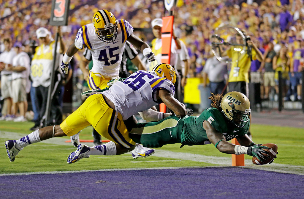 . UAB running back Darrin Reaves (5) scores a touchdown in front of LSU safety Ronald Martin (26) and linebacker Deion Jones (45) in the first half of an NCAA college football game in Baton Rouge, La., Saturday, Sept. 7, 2013. (AP Photo/Gerald Herbert)