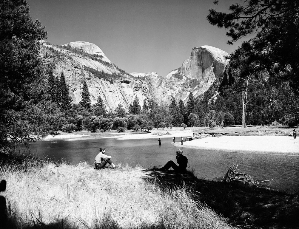. Some of the patients of the Yosemite National Park Naval Convalescent Hospital try their hand at trout fishing in the Merced River which runs through Yosemite Valley, Calif., August 12, 1943. Seated on bank, left, is Joseph P. Clements, PFC in the marines. At right is George Whisman, ship\'s cook 2nd class of Portland, Ore. In left background the North Dome rises 7,531 feet. At right, Half Dome rises 8,852 feet. (AP Photo/Ernest King)
