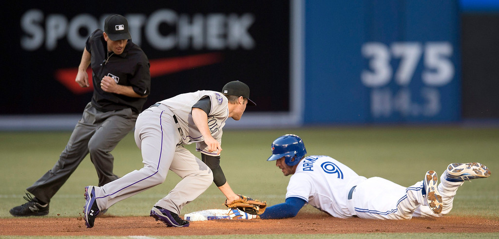 . Toronto Blue Jays\' J.P. Arencibia slides safely into second base for a double as Colorado Rockies\' Josh Rutledge misses the tag during the first inning of an inter-league baseball game in Toronto on Tuesday June 18, 2013.   (AP Photo/The Canadian Press, Frank Gunn)
