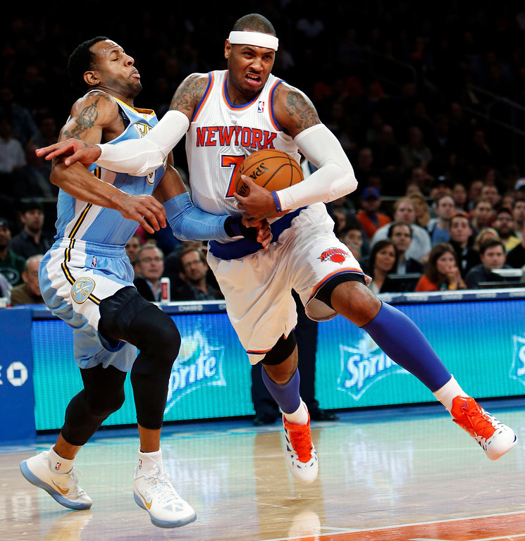 . New York Knicks\' Carmelo Anthony (7) drives against Denver Nuggets\' Andre Iguodala during the first half of an NBA basketball game, Sunday, Dec. 9, 2012, in New York. (AP Photo/Jason DeCrow)