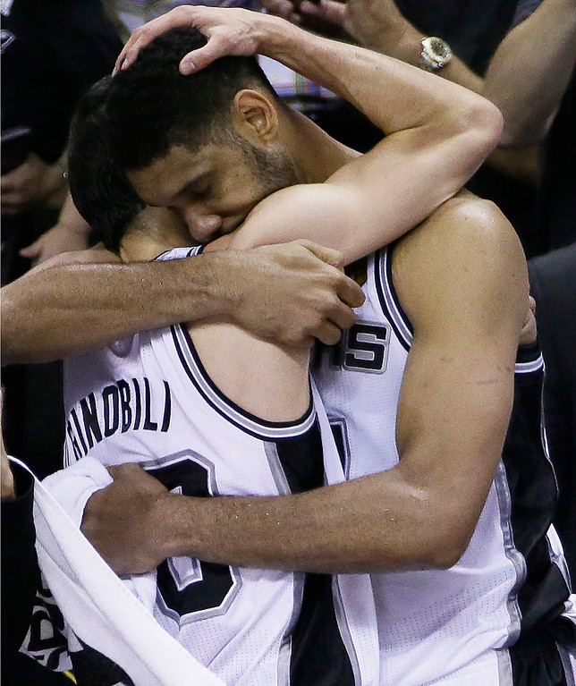 . San Antonio Spurs guard Manu Ginobili, left, and forward Tim Duncan embrace in the final moments of Game 5 of the NBA basketball finals against the Miami Heat on Sunday, June 15, 2014, in San Antonio. San Antonio won the NBA championship 104-87. (AP Photo/Tony Gutierrez)