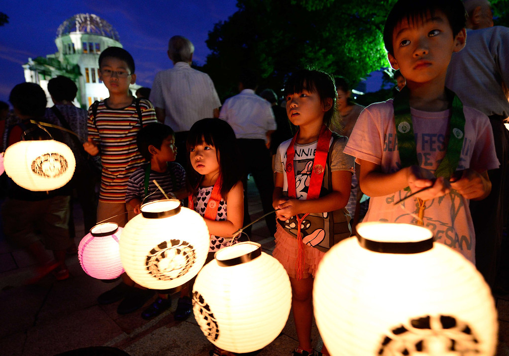 . Children carry lanterns to pray for atomic bombing victims in front of the Atomic Bomb Dome at the Peace Memoral Park in Hiroshima on August 5, 2013. Tens of thousands of people were expected to gather at a peace memorial park in Hiroshima on August 6 to mark the 68th anniversary of the US atomic bombing of the Japanese city. AFP PHOTO / TORU  YAMANAKA/AFP/Getty Images