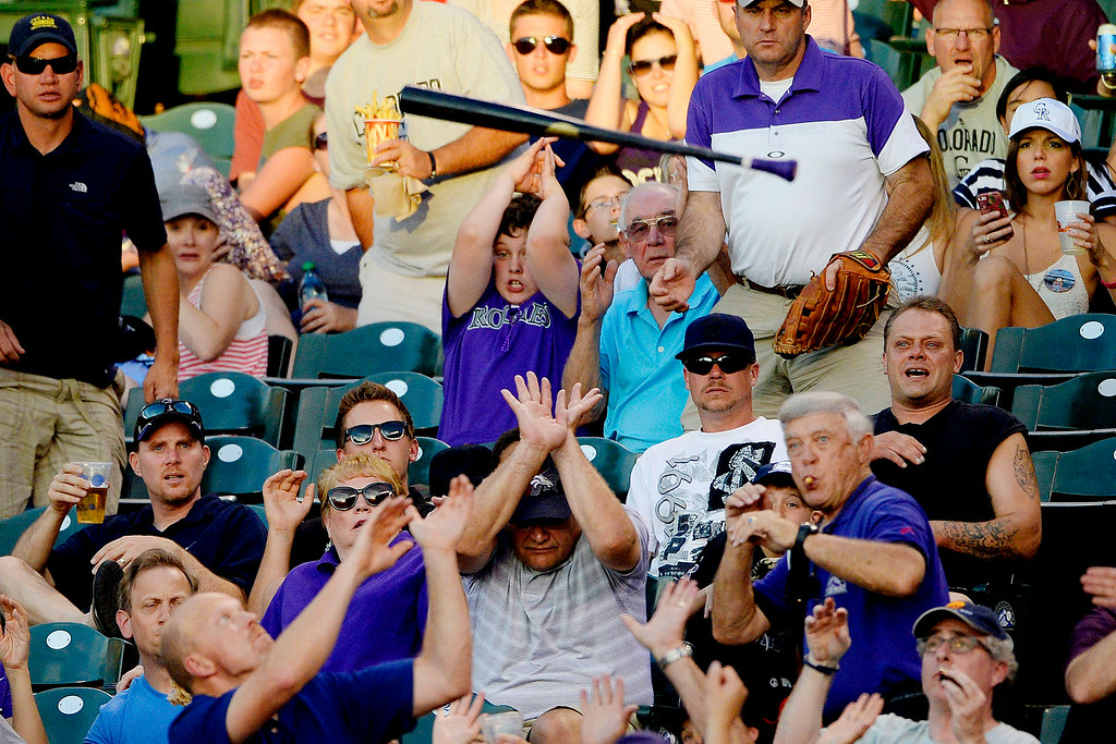 . Fans cover up as a bat belonging to Carlos Gonzalez (5) of the Colorado Rockies flies into the stands during a game against the Washington Nationals at Coors Field. Major League Baseball action between the Colorado Rockies and the Washington Nationals on Monday, July 21, 2014. (Photo by AAron Ontiveroz/The Denver Post)