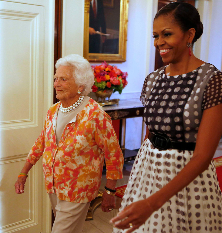 """. Former first lady Barbara Bush (L) and first lady Michelle Obama walk into an event honoring the 5,000th winner of the \""""Daily Point of Light\"""" award in the East Room of the White House in Washington July 15, 2013.      REUTERS/Larry Downing"""